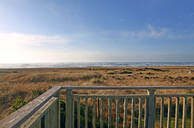 Balcony overlooking grassy field and beach - MINF12488
