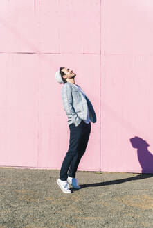 Happy young man in front of pink construction barrier, standing on tiptoes, smiling - UUF17837
