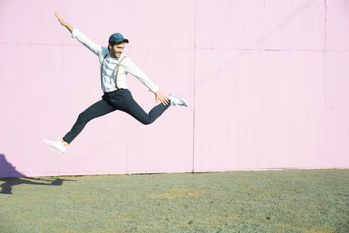Young man in front of pink construction barrier, jumping in the air - UUF17852