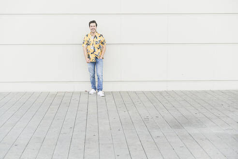 Happy young man wearing aloha shirt, standing against house wall - UUF17864