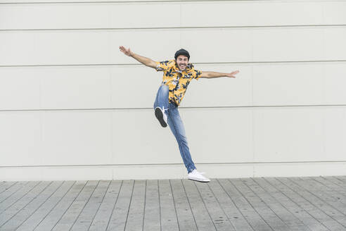 Young man wearing flat hat and aloha shirt, jumping for joy - UUF17867