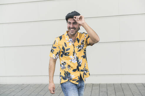 Young man wearing flat hat and aloha shirt, laughing in front of wall - UUF17873