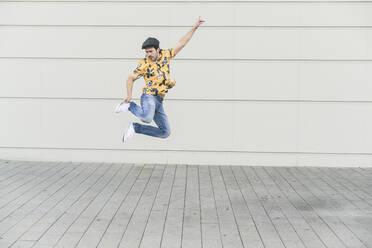 Young man wearing flat hat and aloha shirt, jumping for joy - UUF17876