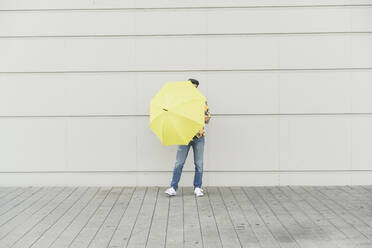 Young man with aloha shirt, holding yellow umbrella - UUF17879