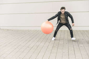 Young man in leather jacket, playing with a gym ball - UUF17891