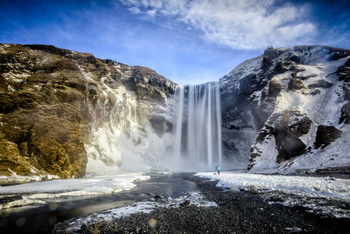 Waterfall pouring over icy cliffs in remote landscape - MINF12565