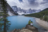 Asian couple sitting on rock admiring scenic view of mountain lake - MINF12664