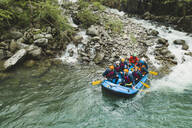 Group of people rafting in rubber dinghy on a river - FBAF00710