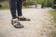 Close-up of man wearing wetsuit and galoshes standing on a path - FBAF00716