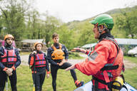Instructor talking to group of friends at a rafting class - FBAF00725