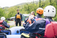 Instructor talking to group of friends at a rafting class - FBAF00728