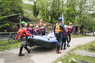 Group of friends preparing for a rafting trip carrying rubber dinghy - FBAF00731