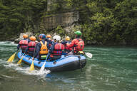 Group of people rafting in rubber dinghy on a river - FBAF00734
