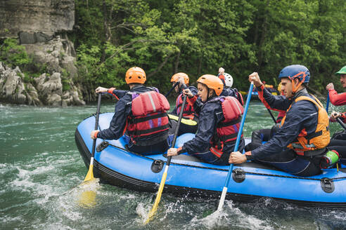 Group of people rafting in rubber dinghy on a river - FBAF00737