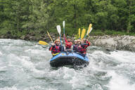 Group of people rafting in rubber dinghy on a river - FBAF00740