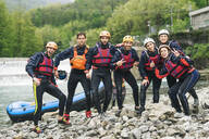 Group of playful friends at a rafting class posing at boat - FBAF00743