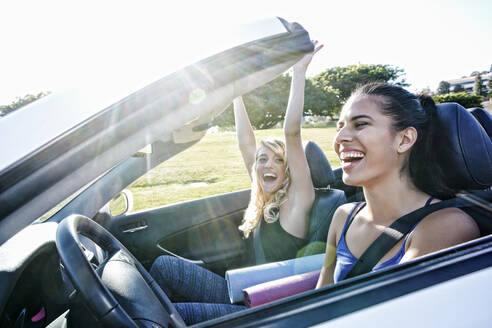 Excited women driving convertible on road trip - BLEF07061