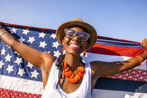 Black woman holding American flag under blue sky - BLEF07100