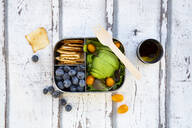 Lunchbox with salad, avocado and yellow tomato, cracker, blueberry and salad dressing, from above - LVF08100