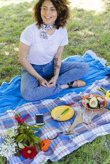 Relaxed smiling woman having a picnic in park - FMOF00689