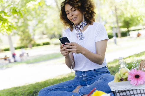 Relaxed woman with cell phone and earphones having a picnic in park - FMOF00698