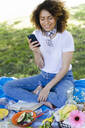 Relaxed woman with cell phone and earphones having a picnic in park - FMOF00701