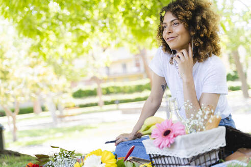 Relaxed woman with cell phone and earphones having a picnic in park - FMOF00704