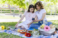 Two women having a picnic and using cell phone in park - FMOF00710