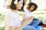Two women with book and headphones relaxing in park - FMOF00716