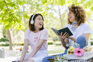 Two happy women with book and headphones relaxing in park - FMOF00719