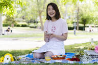 Happy young woman with cell phone and earphones having a picnic in park - FMOF00728