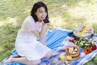 Relaxed woman using cell phone and having a picnic in park - FMOF00731