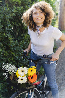 Smiling woman with flowers and bicycle in park - FMOF00746