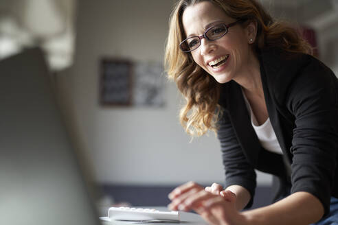 Happy woman using laptop at home - PNEF01632