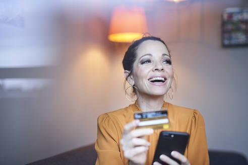 lachende Frau mit Smartphone und Kreditkarte, München, Deutschland - PNEF01644