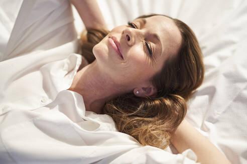 Frau in Schlafanzug auf Bett entspannend, geschlossene Augen Arme hinter Kopf verschränkt, München, Deutschland - PNEF01653