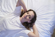 Smiling woman lying in bed with closed eyes - PNEF01656