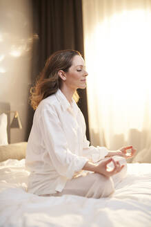 Woman sitting on bed in yoga pose - PNEF01671