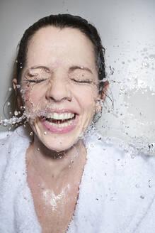 Lachende mittelalte Frau in weissen Bademantel, bekommt Wasser ins Gesicht gespritzt, München, Deutschland - PNEF01680