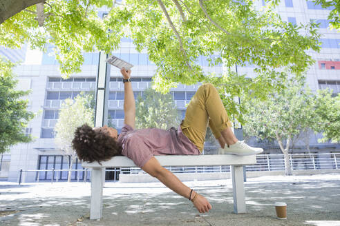 Young man laying on urban park bench and using digital tablet - JUIF01450
