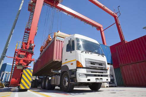 Crane loading cargo container onto lorry at commercial dock - JUIF01474