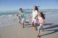 Happy family holding hands and running on sunny beach - JUIF01498