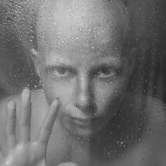 Caucasian woman peering through wet glass - BLEF07297