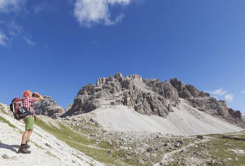 Hiker on hiking trail, Tre Cime di Lavaredo Aera, Nature Park Tre Cime, Unesco World Heritage Natural Site, Sexten Dolomites, Italy - GWF06112