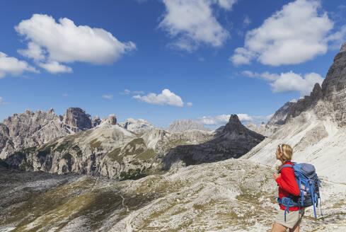 Italy, South Tyrol, Alto Adige, Sextner Dolomiten, Dolomites, Naturpark Drei Zinnen (Parco Naturale Tre Cime di Lavaredo) region, woman enjoying view of Dolomites, Drei Zinnen Hut region (in distance), hiker on trail to hut (kleine Leute), most polupar trail in region, Unesco Welterbe Region - GWF06115