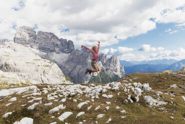 Female hiker jumping, Tre Cime di Lavaredo Area, Nature Park Tre Cime, Unesco World Heritage Natural Site, Sexten Dolomites, Italy - GWF06127