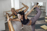 Two young women doing barre workout in gym - VPIF01264