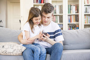 Teenage boy sitting with his little sister on the couch at home looking at cell phone - LVF08110
