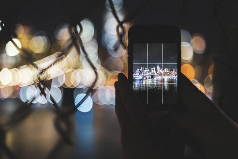 Close-up of woman taking smartphone picture of skyline at night, Manhattan, New York City, USA - MMAF01052