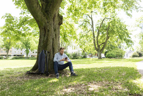 Businessman with E-Scooter leaning against tree trunk at city park using smartphone - JOSF03296